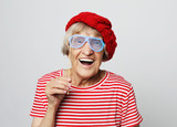 lifestyle, emotion  and people concept: funny grandmother with fake glasses, laughs and ready for party