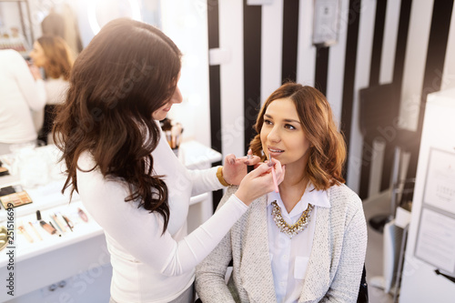 Beautiful caucasian brunette sitting in beauty salon while makeup artist putting lipstick on her lips.