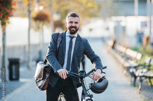 Leinwanddruck Bild Businessman commuter with bicycle walking home from work in city.