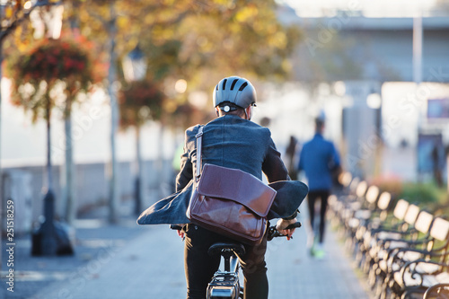 Leinwanddruck Bild A rear view of businessman commuter with electric bicycle traveling to work in city.