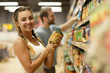 Charming and beautiful young woman with braids holding jar with beans. Female customer standing near shelves with cans, looking at camera and smiling. Background of man taking jar from shelf.