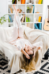 Laughing blonde woman in pyjamas lying on sofa with closed eyes © LIGHTFIELD STUDIOS