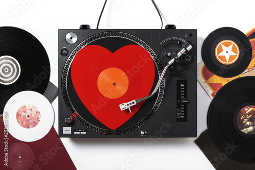 Varna, Bulgaria, January 2019, turntable Numark: Top view of a turntable with red heart-shaped vinyl record a stylus with a needle, on white background with black, white vinyl records. Valentine's Day - 251607439