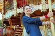 happy stylish traveller woman riding on carousel