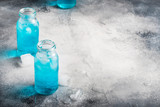 Sport and fitness drink concept, very cold refreshing isotonic blue water in bottles, gray table background, selective focus