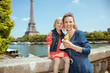 mother and daughter travellers with croissant in Paris, France