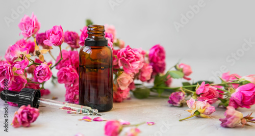 Leinwanddruck Bild Rose oil. Spa and aromatherapy rose flowers essential oil bottle with pipette