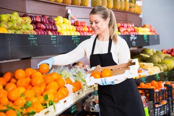 Salesgirl arranging goods in greengrocery