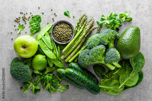 Leinwanddruck Bild Healthy vegetarian food concept background, fresh green food selection for detox diet, raw broccoli, apple, cucumber, spinach, peas, asparagus, avocado, lime, corn salad and mung bean, view from above