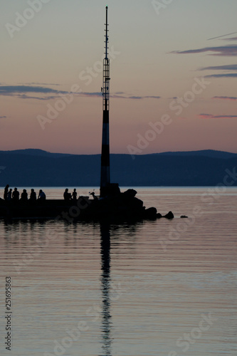 Acrylglas Pier Twilight on Lake Balaton. A warm, quiet summer evening. People sitting on the breakwater. Visible mountains in the background. The reflection of the mast on the surface of the water. A beautiful dusk.