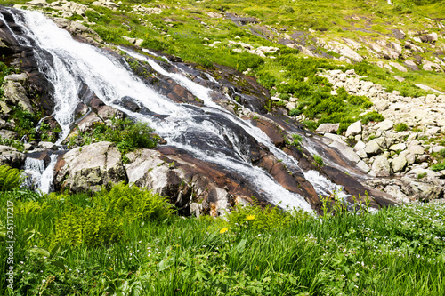 Spring waterfall in mountain valley. Fast river with green shores © Koirill