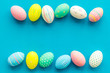 Easter composition. Decorated pastel Easter eggs on blue background top view copy space
