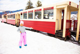 Little smiling girl in winter cloths inviting to enter old narrow train in Georgia