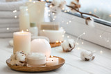 Beautiful burning candles with jar of cream on windowsill