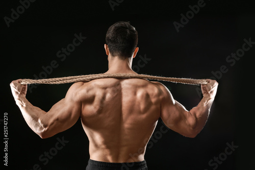 Leinwandbild Motiv Muscular bodybuilder with rope on dark background, back view