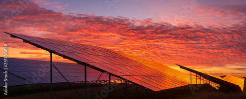 Leinwandbild Motiv Solar power plant on the background of dramatic, fiery sky at sunset,Germany