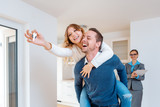 Man carrying his wife piggyback who is showing the house keys