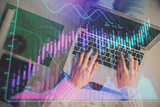 Hands typing on laptop. Business and Financial concept. Double exposure of stock market charts. - 251768224
