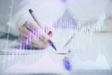 Close up of hands writing with double exposure of business charts. Financial concept. - 251768297