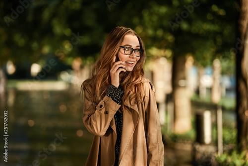 obraz lub plakat Portrait of beautiful woman using cell phone while walking through empty boulevard