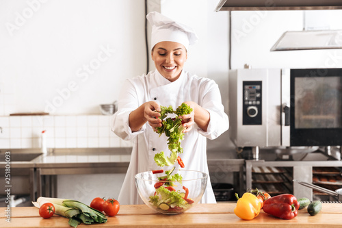 Photo of pleased woman chef wearing white uniform making salad with fresh vegetables, in kitchen at the restaurant - 251800093