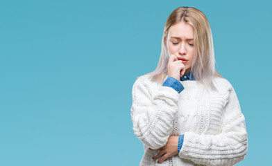 Young blonde woman wearing winter sweater over isolated background looking stressed and nervous with hands on mouth biting nails. Anxiety problem.