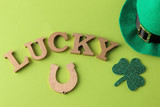 St.Patrick 's Day. holiday. Green hat of leprechaun, horseshoe and text on a bright green background. view from above.