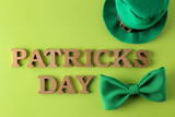 St.Patrick 's Day. celebration. A green bow tie, a leprechaun hat  and the text of March 17 on a bright green background. top view.