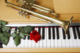 Trumpet and red rose on the piano keyboard.