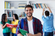 Leinwanddruck Bild - Lachender spanischer Student in der Uni-Bibliothek