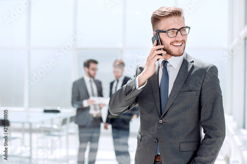 businessman with mobile phone standing next to the Bank office © ASDF