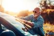 Leinwandbild Motiv Senior man cleaning his car outdoors