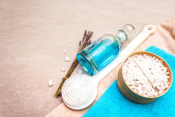 Spa concept, natural ingredients. Bath towels, sea salt with lavender, shower gel, brush. On a stone background © FuzullHanum