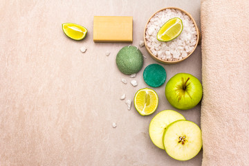 Spa concept, natural ingredients. Bath towel, sea salt with lime, apple, olive and mint soap, sponge. On a stone background, top view © FuzullHanum