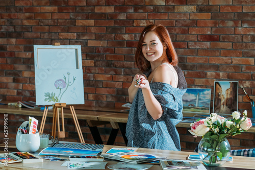 Art hobby. Studio workspace atmosphere. Smiling redhead female posing with paintbrushes and easel in background. © golubovy