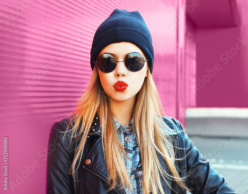 Fashion portrait blonde woman sending sweet air kiss in rock black style jacket, hat posing on city street over colorful pink wall background