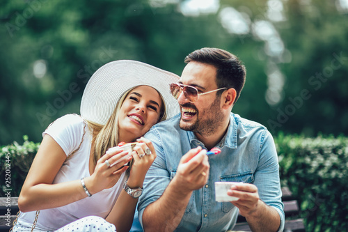 Couple joking and having fun while eating an ice cream in the park. - 252002445