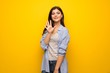 Teenager girl over yellow wall counting five with fingers