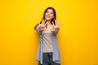 Teenager girl over yellow wall counting ten with fingers