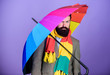 Man bearded hipster hold colorful umbrella. It seems to be raining. Rainy days can be tough to get through. Prepared for rainy day. Carefree and positive. Enjoy rainy day. Weather forecast concept