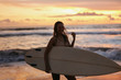 Leinwandbild Motiv Summer. Surfer girl silhouette with surf board on sunset beach