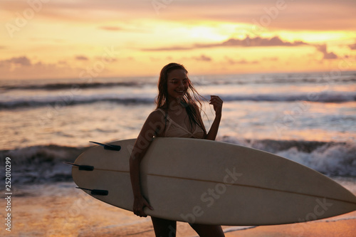 obraz PCV Summer. Surfer girl silhouette with surf board on sunset beach