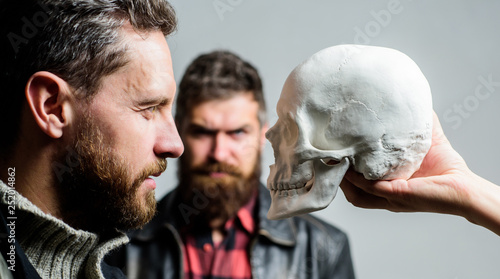 Be brave. Focused on breaking fear. Psychology concept. Human fears and courage. Looking deep into eyes of your fear. Man brutal bearded hipster looking at skull symbol of death. Overcome your fears