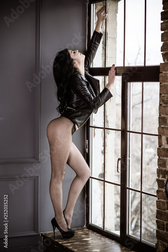 Sexy thin woman wear leather jacket and tights in the net , erotic photo of seductive young woman