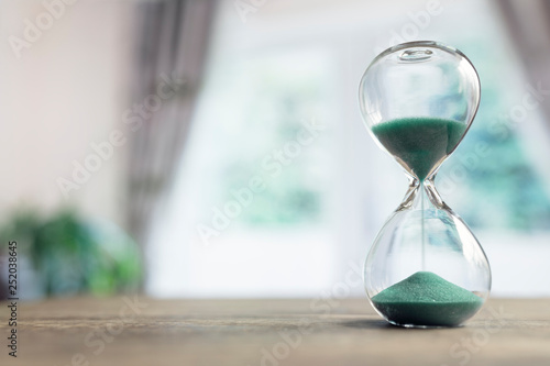 Leinwanddruck Bild Hourglass time passing in room by window
