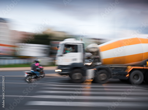Dangerous city traffic situation with a motorcyclist and a truck