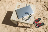 Laptop sunglasses and male flip flops on the beach