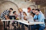 Grupa młodzi ludzie biznesu w mądrze przypadkowej odzieży pracuje wpólnie w kreatywnie biurze