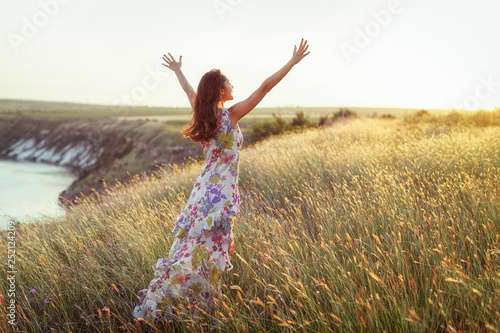 Happy woman in light dress standing in grass