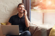 Leinwandbild Motiv Laughing man with laptop speaking on phone